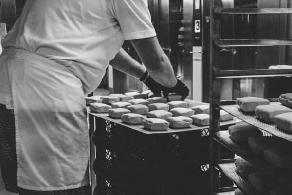 Ein Bäcker beim Brötchen absetzen, genau die bestellte Anzahl wird gebacken