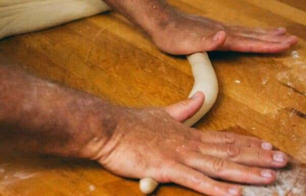 Ein Bäcker rollt den Teig für unser Laugengebäck