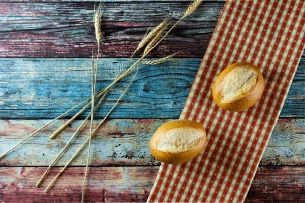 Schrippen, klassische Weizenbrötchen mit Getreideähre auf Tischdecke