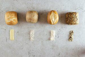 Vier Brötchen mit Zutaten auf einer Steinplatte