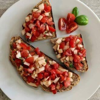 Bruschetta mit Roggenbrot, Zwiebeln, Tomaten, Knoblauch und Basilikum